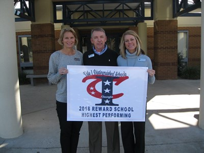 Middle school administrators holding banner that says 2018 Title I Highest Performing Reward School